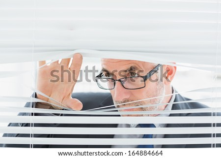 Close-up of a serious mature businessman peeking through blinds in the office