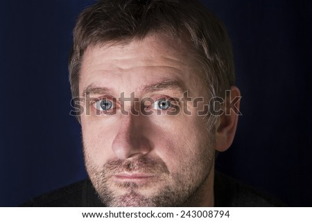 Close up of a serious unshaven man, horizontal studio shot - stock photo