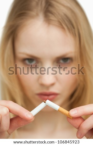Close up of a serious woman breaking a cigarette against white background