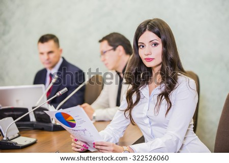 close up of a serious young businesswoman with colleagues in meeting in background at the office