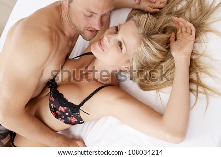 Close up of a sexy couple kissing and playing in bed. - stock photo