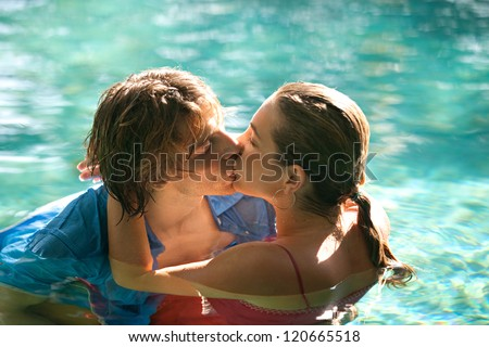 Close up of a sexy young couple submerged in a swimming pool while dressed, hugging and kissing while on a tropical destination vacation. - stock photo