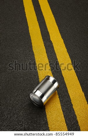 Close up of a shiny metal can sitting on a black asphalt road with yellow stripes. - stock photo