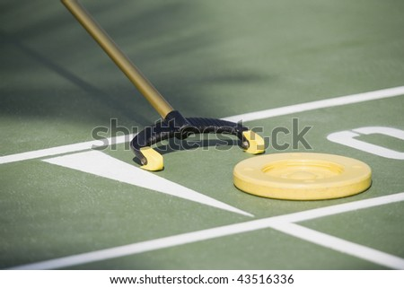 Close-up of a shuffleboard disc and shuffleboard cue - stock photo