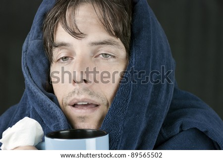 Close-up of a sick man holding a tissue and a hot mug. - stock photo