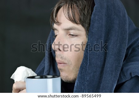 Close-up of a sick man holding a tissue blowing on a hot mug. - stock photo