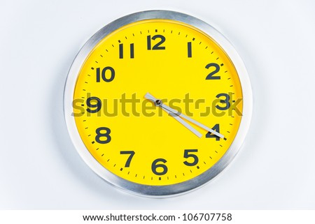 close-up of a silver and yellow wall clock. - stock photo