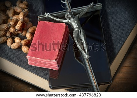 Close up of a silver crucifix with wooden rosary beads on a smart phone and two Holy Bibles - stock photo