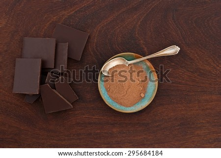 close up of  a silver spoon, chocolate and cacao powder on wooden background - studio shot  from above - stock photo