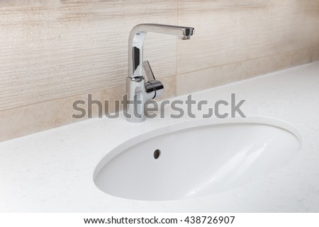 Close-up of a sink and a mixer mounted in a stone counter in a bathroom