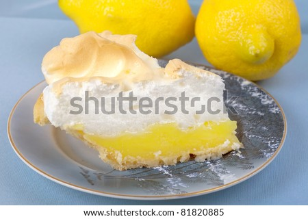 Close up of a slice of homemade lemon meringue pie on an antique plate. - stock photo