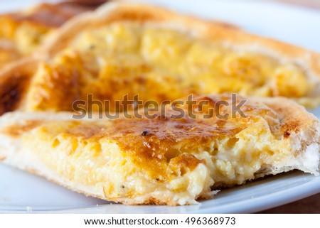 Close-up of a slice of welsh rarebit, a type of cheese on toast, with a bite taken out of it