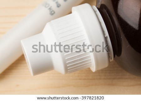 Close up of a small glass bottle (pill/sirup bottle) on table. Selective focus. Macro.