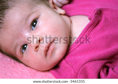 close up of a small one week old newborn baby on a pink background - stock photo