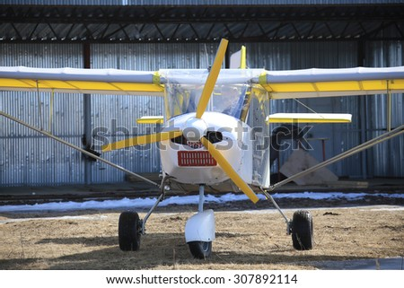close-up of a small plane near hangar early spring - stock photo
