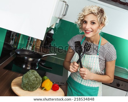 Close up of a smile woman cook holding ladle spoon fork - accessories in the kitchen. Prepare healthy food - vegetable