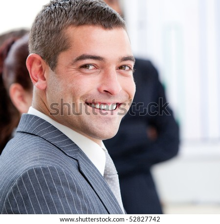Close-up of a smiling businessman at a presentation with his team