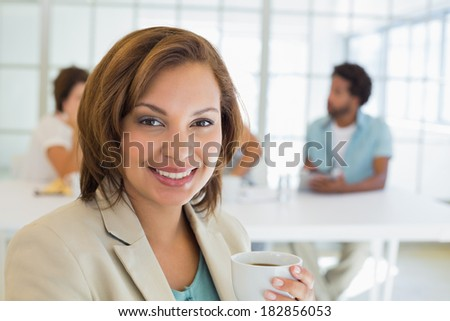 Close-up of a smiling businesswoman having coffee with colleagues in meeting in background at the office