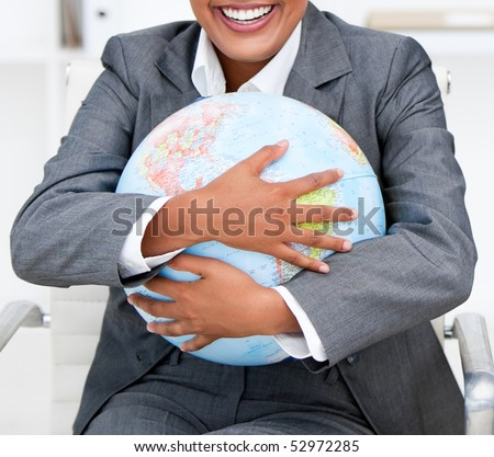 Close-up of a smiling businesswoman holding a terrestrial globe in the office - stock photo