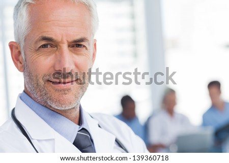 Close up of a smiling doctor sanding in front of his team - stock photo
