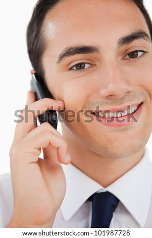 Close-up of a smiling man in a suit calling with his cellphone against white background