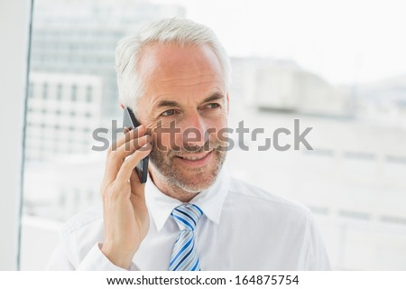 Close-up of a smiling mature businessman using mobile phone in a bright office