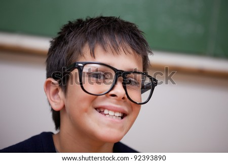Close up of a smiling schoolboy in a classroom - stock photo