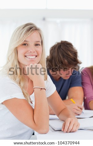 Close up of a smiling student with her friends as they all study while she looks into the camera - stock photo