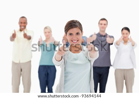 Close-up of a smiling woman giving the thumbs-up with people behind against white background - stock photo
