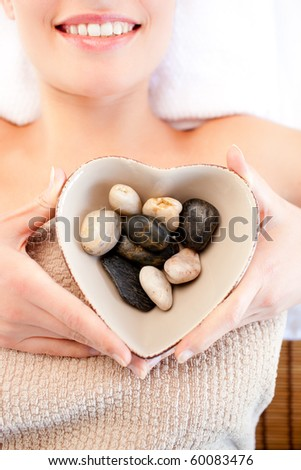 Close-up of a smiling woman holding a bowl in the shape of a heart with pebbles in a spa center - stock photo