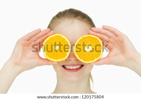 Close up of a smiling woman placing oranges on her eyes against white background
