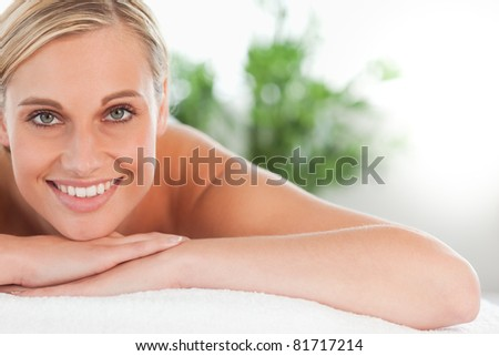 Close up of a smiling woman relaxing on a lounger in a wellness center