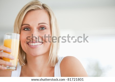 Close up of a smiling woman toasting with orange juice in the kitchen - stock photo
