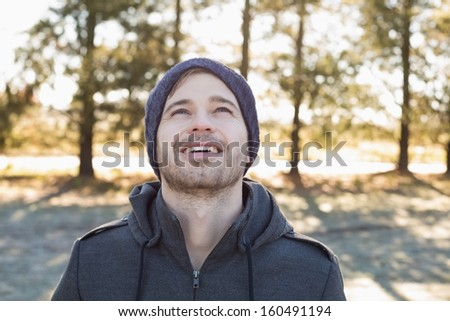 Close-up of a smiling young man in warm clothing looking up in forest on a winter day - stock photo