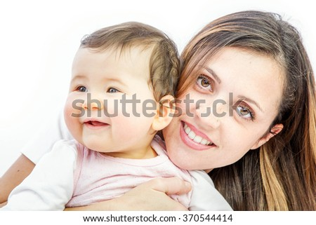 close-up of a smiling young woman with her baby on white background - stock photo