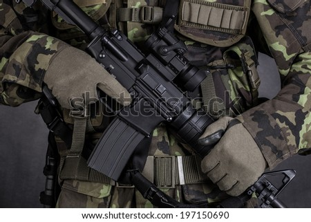 Close-up of a soldier holding modern weapon M4 carbine - stock photo