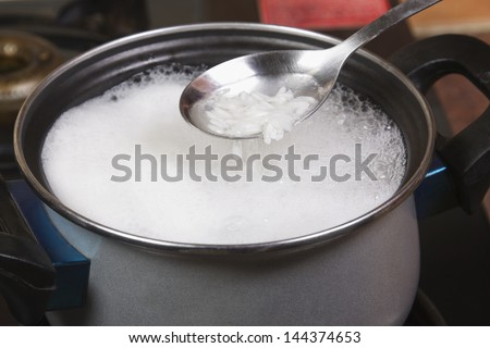 Close-up of a spatula over a pan of rice boiling on a stove
