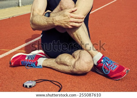Close up of a sportive man who is stretching  with stop watch  on a stadium tartan surface after workout.