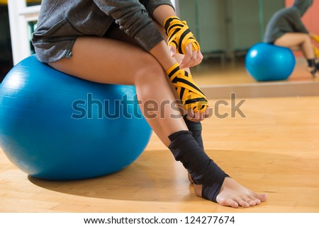Close-up of a sportswoman sitting on a gym ball - stock photo