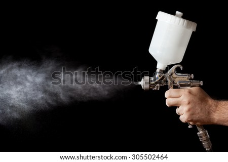 Close up of a spray paint gun with black background - stock photo