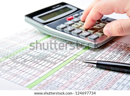 Close-up of a spreadsheet with pen and calculator. - stock photo