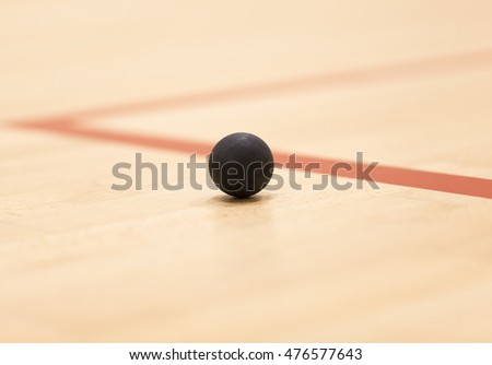 Close up of a squash ball over wooden background
