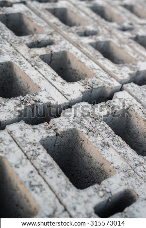 Close-up of a stack of hollow, gray concrete blocks at a building site. - stock photo