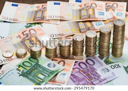 Close-up Of A Stacked Coins Arranged On Euro Banknotes - stock photo
