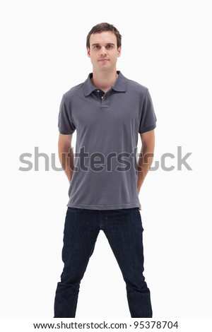 Close-up of a standing man with his hands behind his back and his legs apart against white background - stock photo
