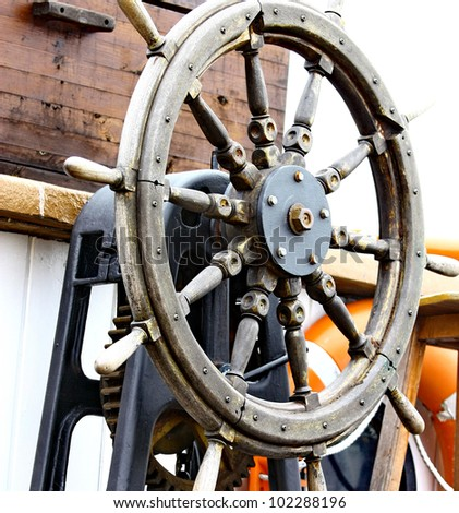 Close up of a steering wheel of the ship made of a wood