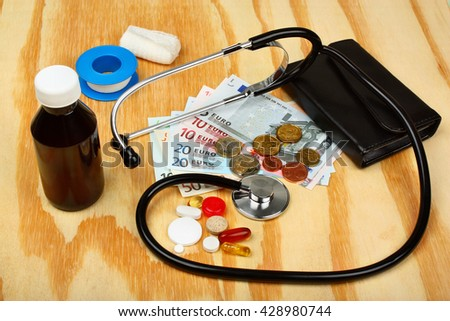 Close up of a stethoscope with some pills on a wooden table - stock photo