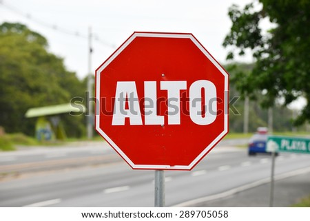 Close up of a stop sign in spanish before an intersection - stock photo