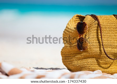 Close up of a straw bag, sun glasses and towel on a tropical beach - stock photo