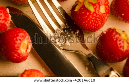 Close-up of a strawberry and a fork - stock photo